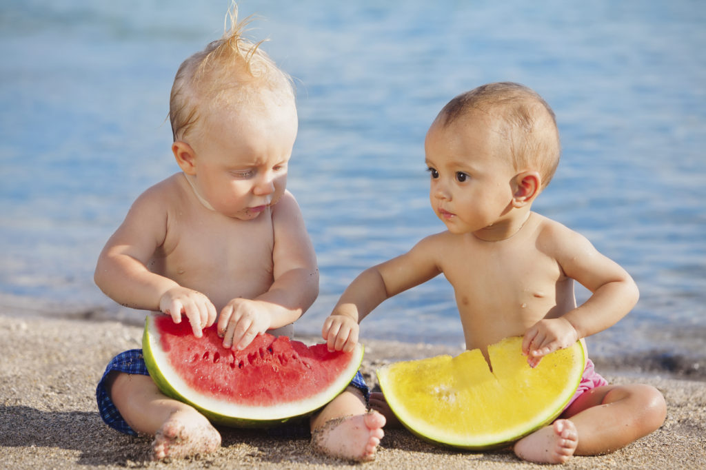 On beach asian and caucasian babies eat fruits fresh watermelons